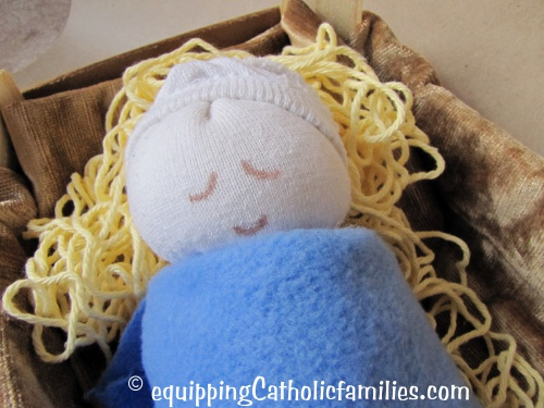 Sock Baby Jesus with string straw in a clementine box crib